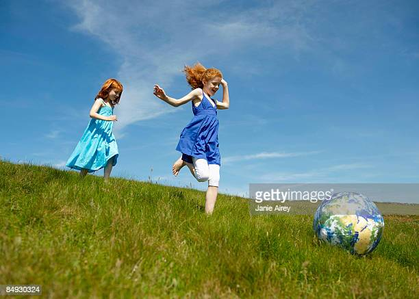 2 young girls running with ball (globe)