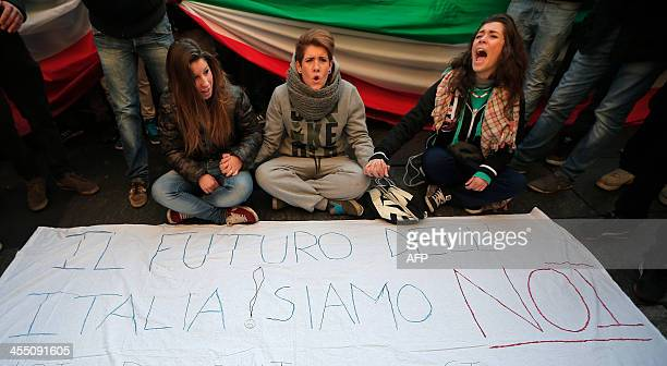 """Young girls shout slogans as they sit behind a poster reading """"The Future of Italy ! We are.""""during a protest against austerity measures in """"Piazza..."""