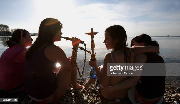 Young girls sit at the beach of Lake Constance sucking a sheesha on April 17 near Lindau Germany The unseasonably warm weather has heralded the start...