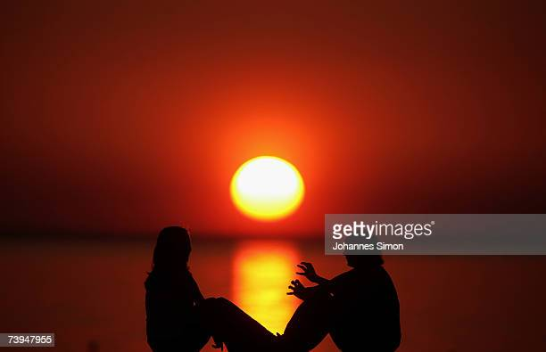 Young girls sit on a pier at the beach of Lake Constance during sunset on April 22 in Langenargen Germany According to weather forcasts the unusual...