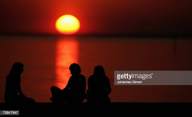 Young girls sit on pier at the beach of Lake Constance during sunset on April 22 in Langenargen Germany The warm and fine April weather will continue...