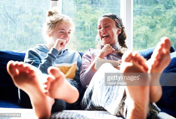 young girls sitting on a couch looking at a screen and laughing - ナイトウェア ストックフォトと画像