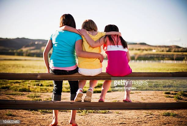 3 young girls sitting on fence - only girls stock pictures, royalty-free photos & images