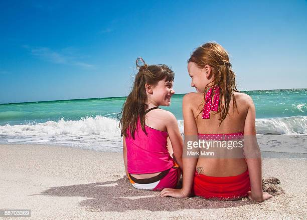 young girls sitting on the beach watching the wave - captiva island - fotografias e filmes do acervo