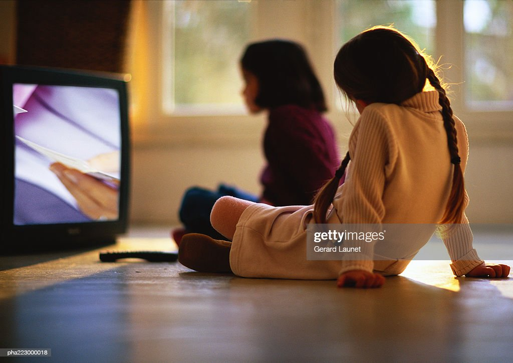 Young girls sitting on wood floor watching TV, girl in background blurred. : Stockfoto