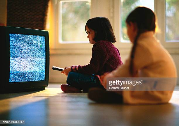 Young girls sitting on wood floor watching TV, girl in foreground blurred.