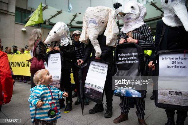 Young girls smiles at climate activists from Exctinction Rebellion dressed as endangered animals as they occupy the forecourt of BBC New Broadcasting...