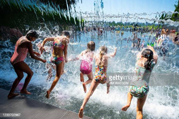Young girls splash through a waterfall at a park in Washington, DC, on June 28 as a heatwave moves over much of the United States. - Swathes of the...