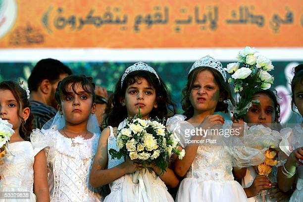 Young girls stand on stage during a mass wedding organized by the Palestinian party Hamas August 5 2005 in Gaza City the Gaza Strip The brides have a...