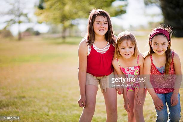 3 young girls standing in line laughing - only girls stock pictures, royalty-free photos & images