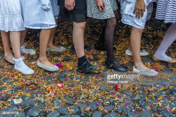 Young girls strain under weight of religious float on a cobblestone street