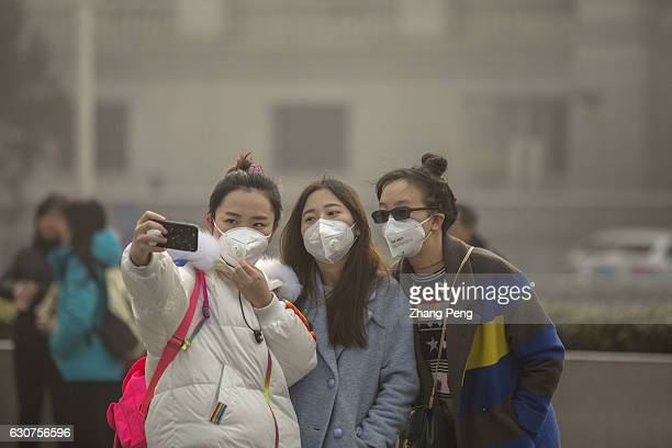 Young girls take selfie in heavy haze wearing special masks to prevent breathing in the toxic air particles On the first day of 2017 Beijing suffered...
