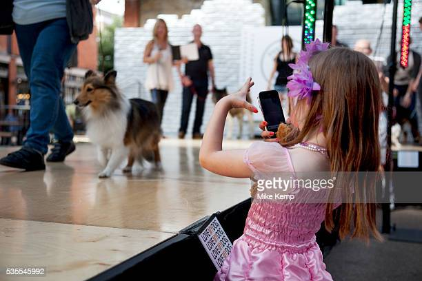 A young girls takes a photo on her phone at Paw Pageant dog show at Spitalfields Market London Local people enter their dogs into the Shoreditch...