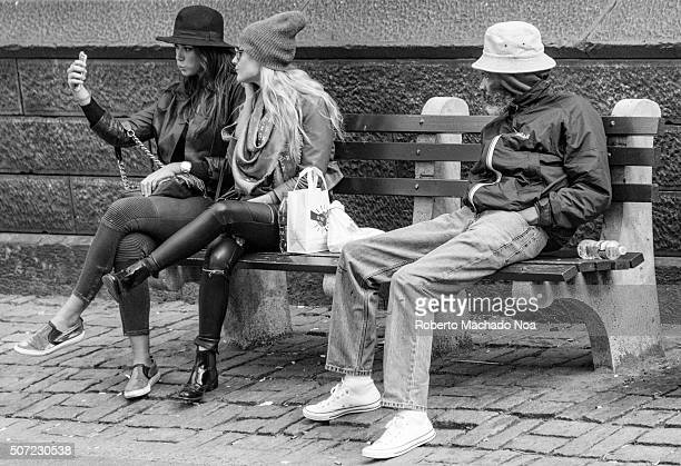 Young girls taking selfie while old man watches them sitting on a street bench in New York City USA With advancement in technology the generation gap...