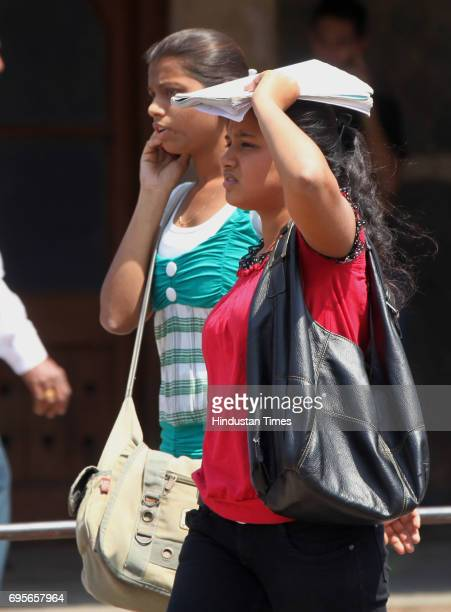 Young girls use books to cover their faces from the scorching sun outside Bandra staion as city experiencs a steady rise in mercury laast few days
