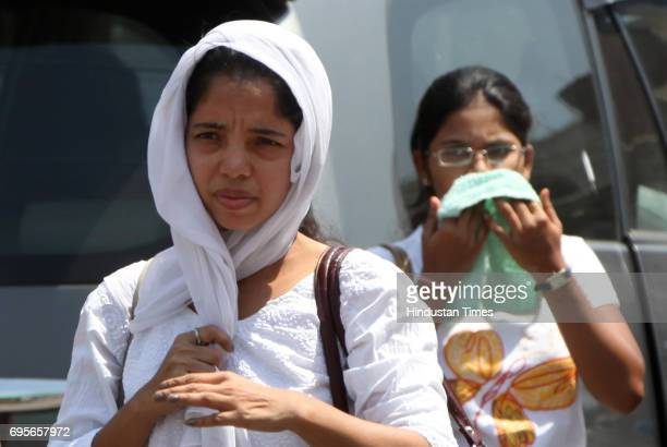 Young girls use their pallu to cover their faces from the scorching sun outside Bandra staion as city experiencs a steady rise in mercury laast few...