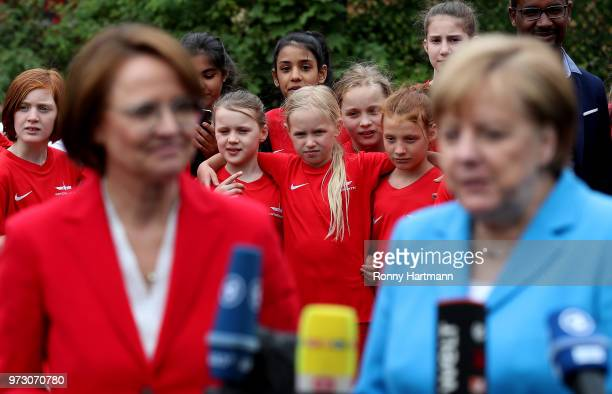 Young girls wait behind German Chancellor Angela Merkel and Federal Commissioner for Migration Refugees and Integration Annette WidmannMauz as they...