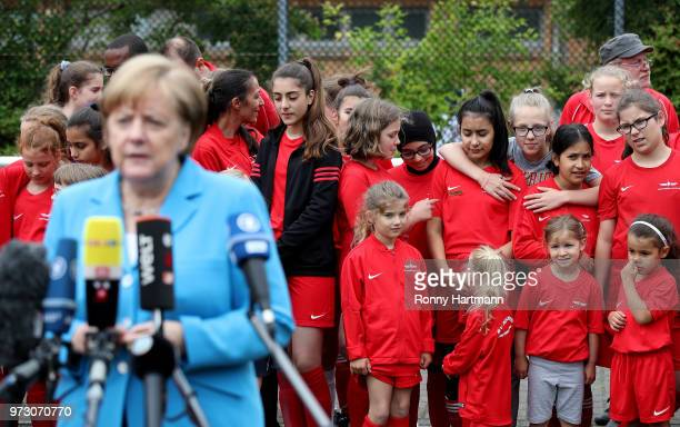 Young girls wait behind German Chancellor Angela Merkel as she speaks to the media at the conclusion of her visit to a program to encourage...