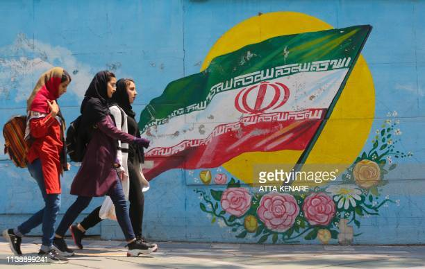 TOPSHOT Young girls walk in front of a mural showing the Iranian national flag in the centre of the capital Tehran on April 23 2019 The White House...