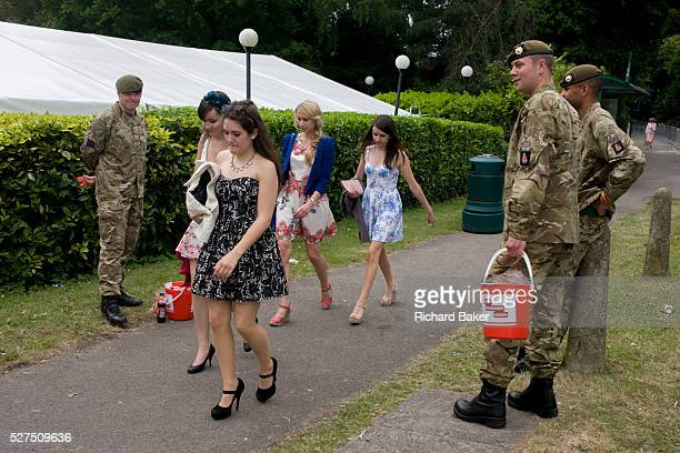 Young girls walk past soldiers from the Coldstream Guards after a day's racing during the annual Royal Ascot horseracing festival in Berkshire...