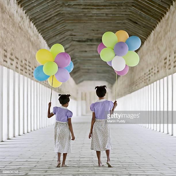 young girls walking along temple corridor