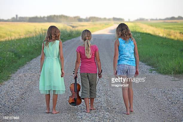 Young Girls Walking Down Rural Gravel Road in Summer
