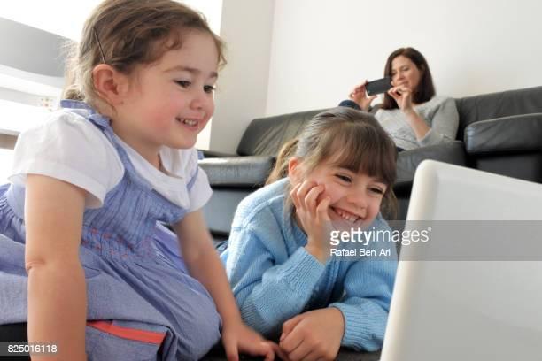 young girls watching program on a wireless device - rafael ben ari stock-fotos und bilder