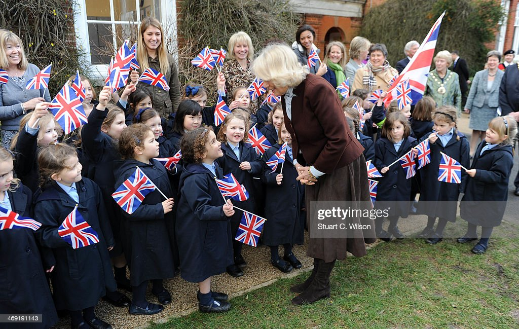 Young girls wave the union jack flag as Camilla, Duchess Of Cornwall visits St Catherine's School in Bramley, Surrey on February 13, 2014 in Guildford, England.