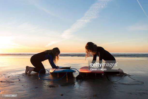 young girls waxing their surfboards at sunset - depilazione intima foto e immagini stock