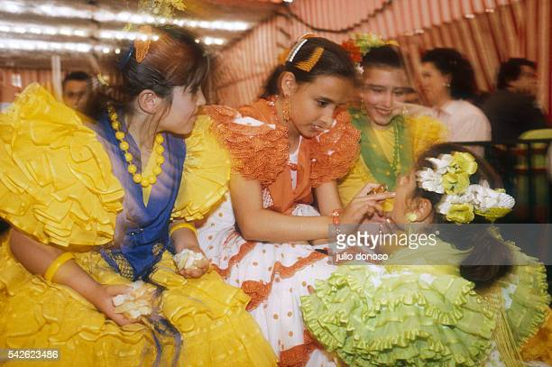 Young girls wear colorful ruffled dresses during Abril Feria celebrations in Seville Spain