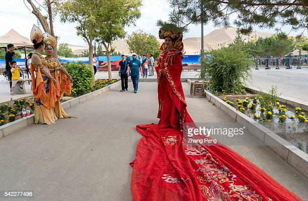 Young girls wear costume of Tang Dynasty or performance as flying Apsaras of Dunhuang caves to attract tourists on the street Serving as an important...