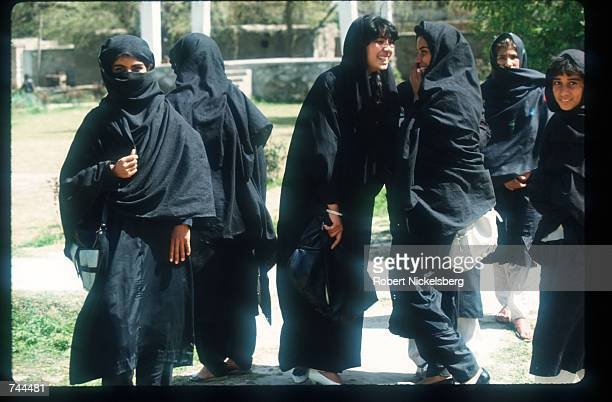 Young girls wearing hijabs and loose clothing walk March 15 1993 in Kabul Afghanistan Since the Islamic government took over Afghanistan women are...
