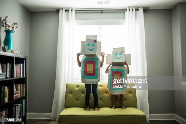 young girls wearing homemade robot costumes at home - innocence stock pictures, royalty-free photos & images