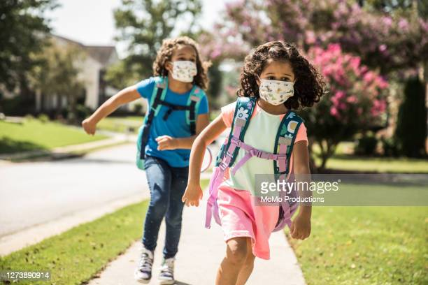 young girls wearing protective masks running on sidewalk - education stock pictures, royalty-free photos & images