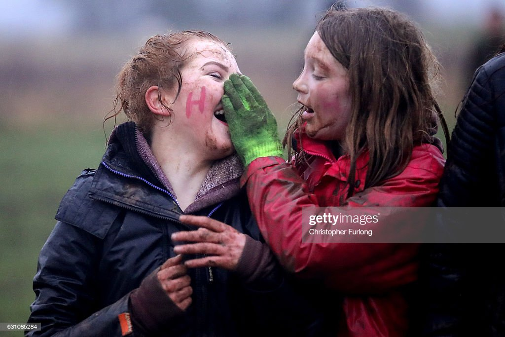 Young girls wipe mud from their faces after wrestling in the fields for the hessian Hood during the junior Haxey Hood game at Haxey Village on January 6, 2017 in Doncaster, England. The origins of the ancient game of Haxey Hood goes back hundreds of years to the 14th century. Lady de Mowbray was out riding towards Westwoodside on the hill that separates it from the village of Haxey, when her silk riding hood was blown away by the wind, farm workers in the field rushed to help and chased the hood eventually it was caught by one of the men, but being too shy to hand it back to the lady, he gave it to one of the others to hand back to her. She thanked the farm worker who had returned the hood and said that he had acted like a Lord, whereas the worker who had actually caught the hood was a Fool. The act of chivalry and the resulting chase amused her so much she donated 13 acres of land on condition that the chase for the hood would be re-enacted each year.