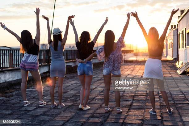 Young girls with arms up on roof at sunset. Copy space.