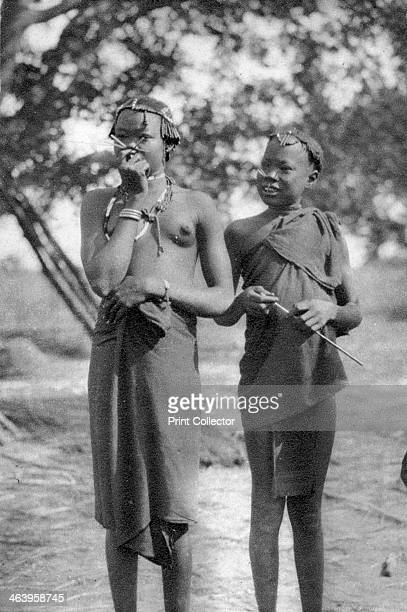 Young girls with sticks in their noses and lips, Terrakekka to Aweil, Sudan, 1925 . A print from Cape to Cairo, by Stella Court Treatt, George G...
