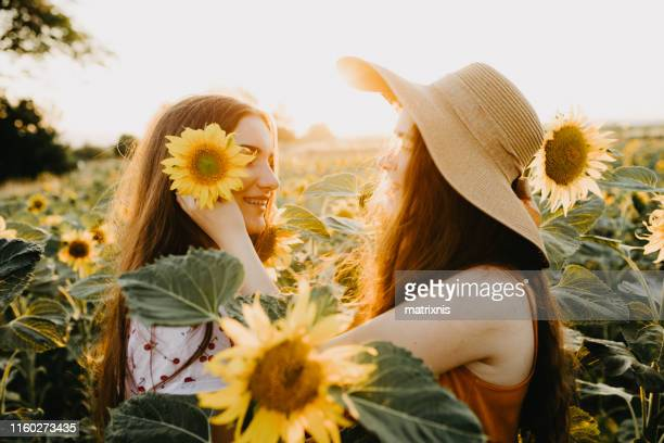 Young girls  with summer hat in a sunflower field