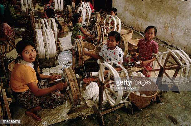 Young girls work in a factory transferring bundles of cotton yarn to bobbins to be used in handlooms Madjalaja village near Bandung Java | Location...