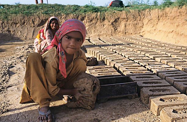 Young girls working in a brick kiln in the open air and leaving them out to dry in the sun Punjab India