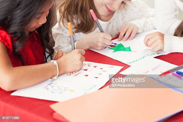 Young girls writing Christmas cards for charity shoe boxes
