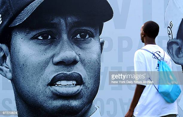 A young golf fan walks by a giant display featuring Tiger Woods' face during practice rounds at the Barclays Golf Tournament at Liberty National Golf...