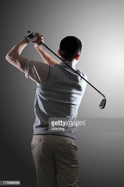 young golf player swinging, rear view - golf swing stock pictures, royalty-free photos & images