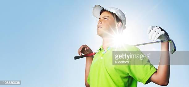Jovem Golfista retroiluminado, por do sol