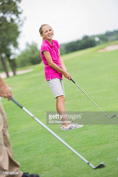 Young golfer girl playing golf with family on course