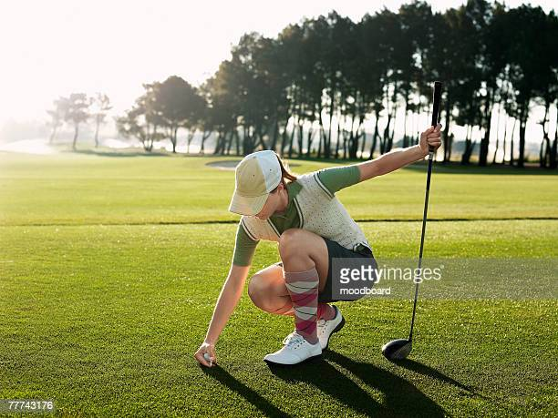 young golfer placing ball on tee - teeing off stock pictures, royalty-free photos & images