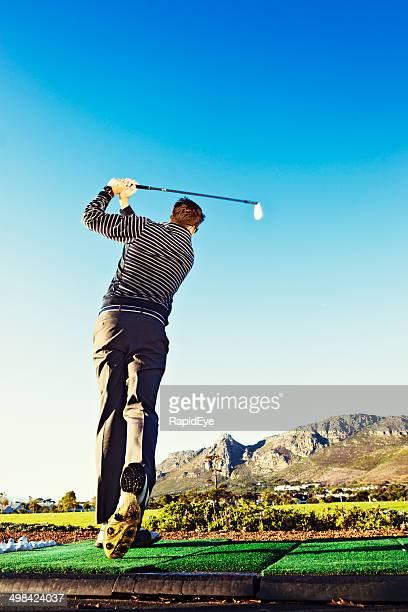 若いゴルファー practising 、ゴルフ練習場、山々を背景にした