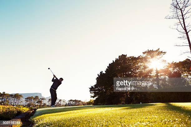 Giovane giocatore di golf, che si stagliano contro Sole di mattina, Tee off
