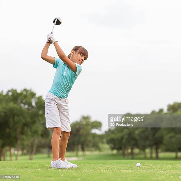 Young golfer teeing off on beautiful golf course