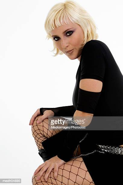 Young Goth woman with bleached hair kneeling